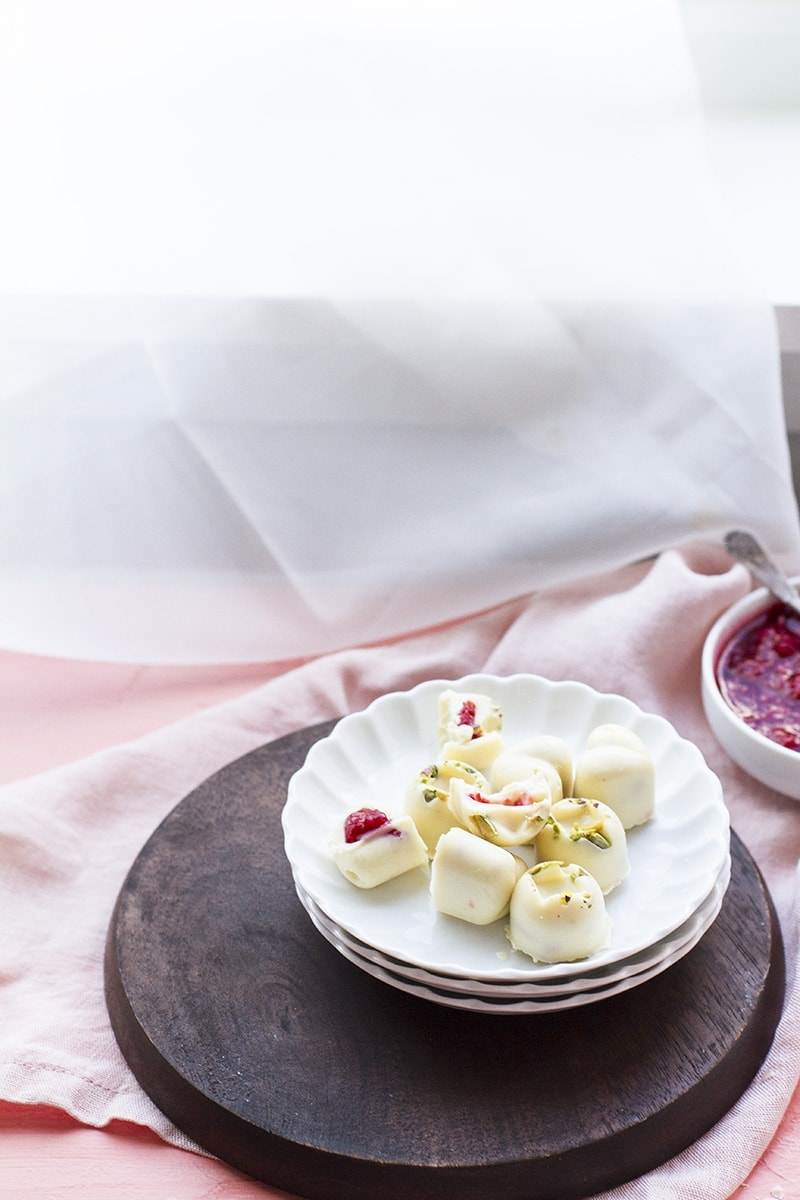 White chocolates on a white plate. See-through curtains behind.
