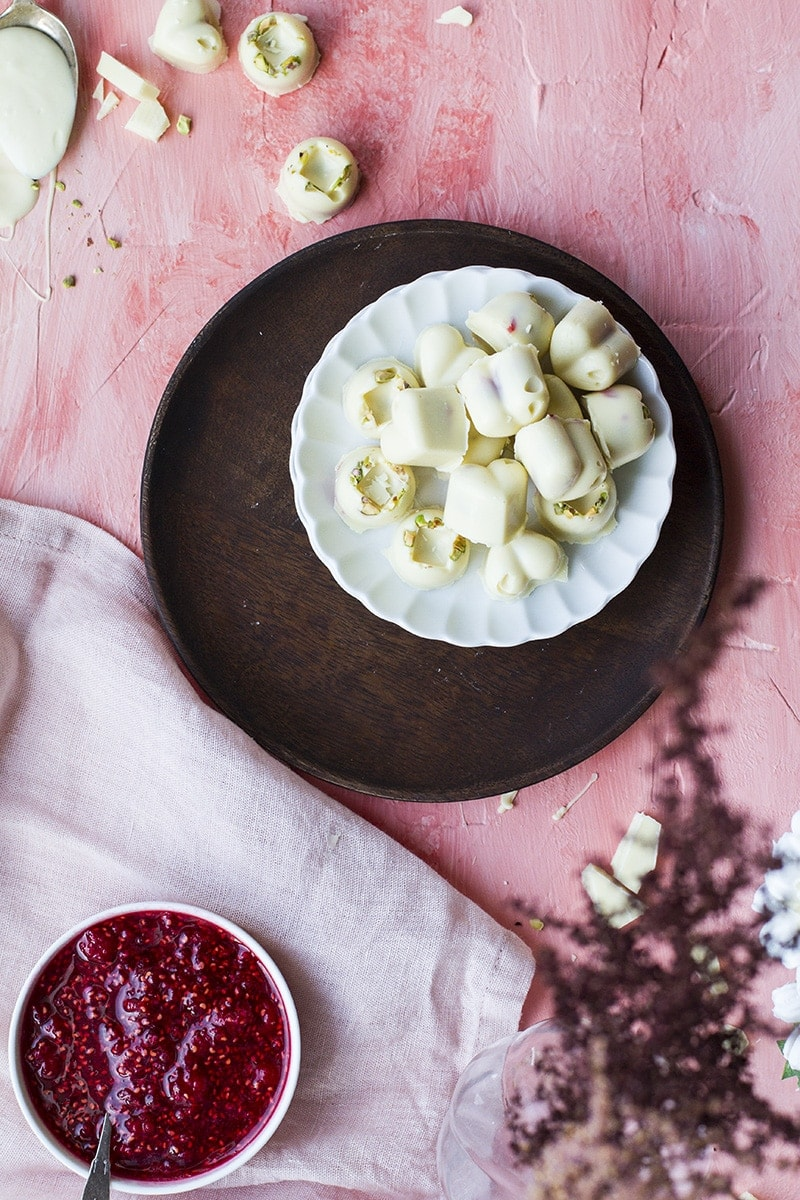 Heart shaped white chocolates and a small bowl of raspberry jam. Pink background.