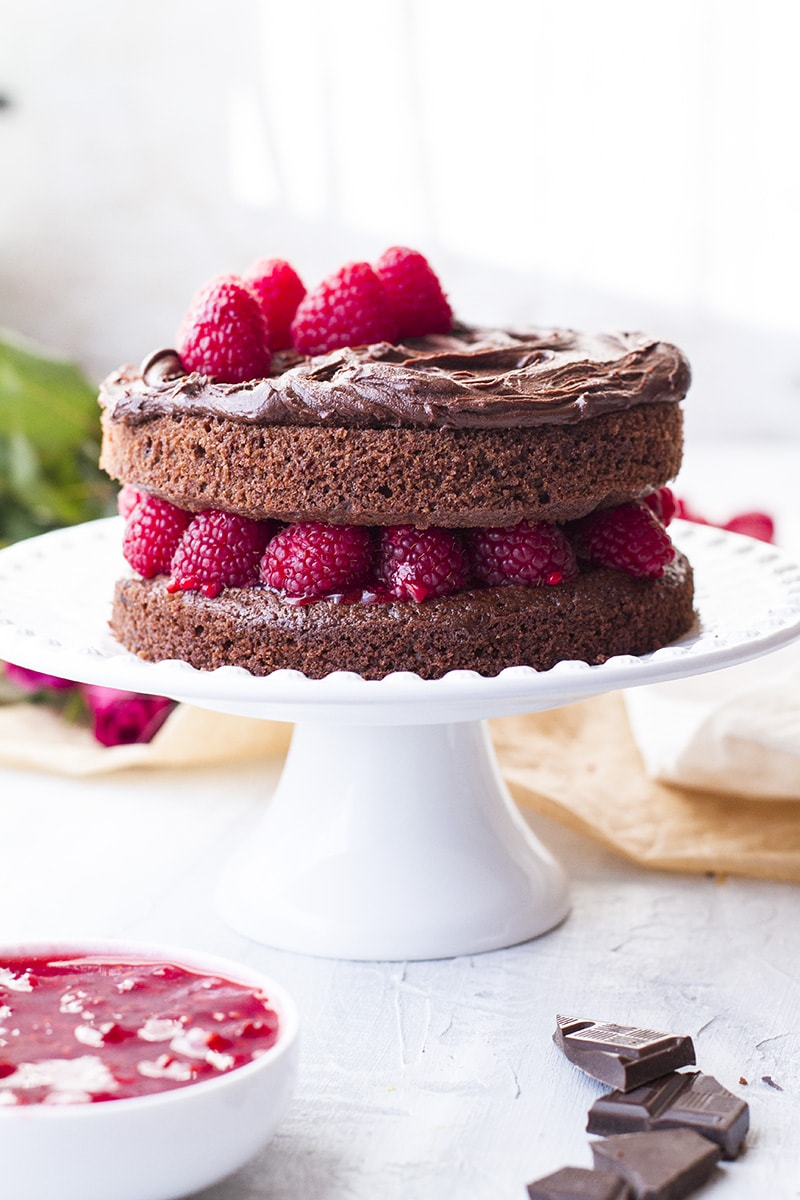 Chocolate cake with raspberry filling on a white cake stand.