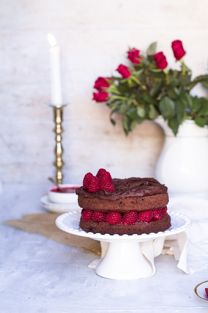 Chocolate raspberry cake on a cake stand, roses in the background.