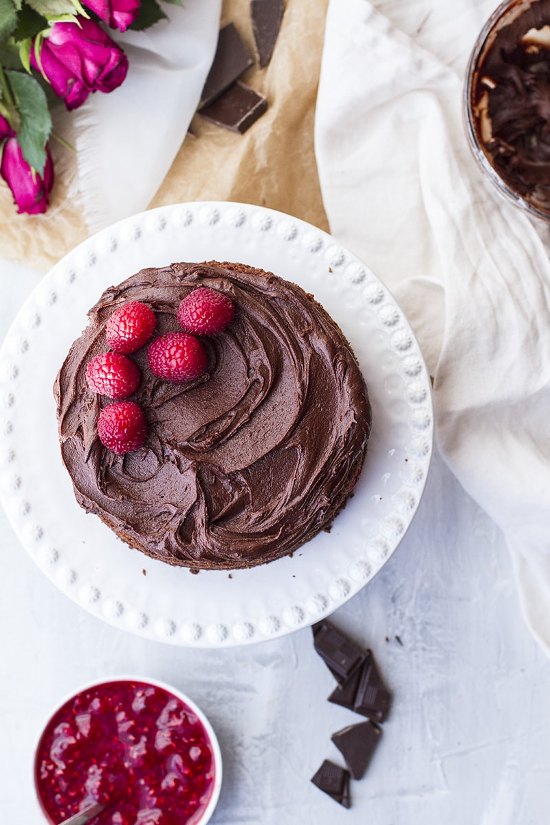 Raspberry chocolate cake on a white cake stand.
