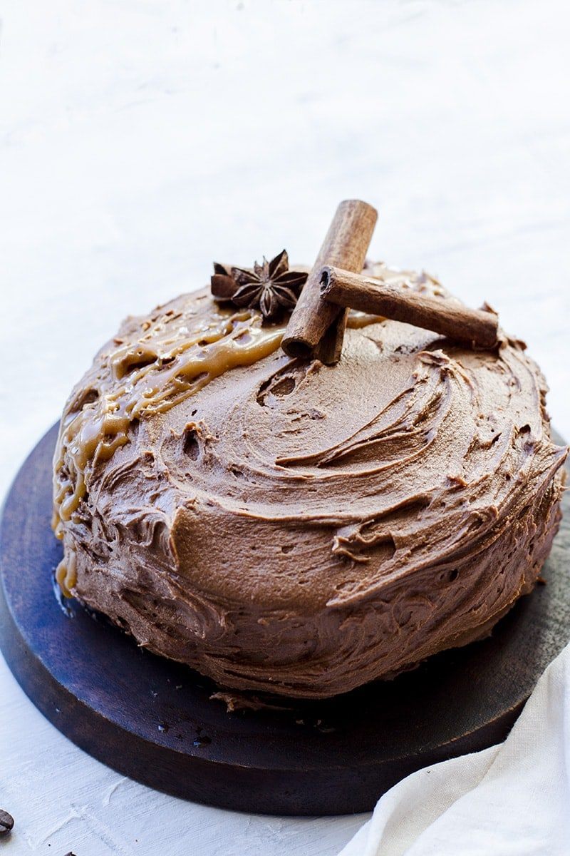 Cake with chocolate buttercream on a wooden cake stand.