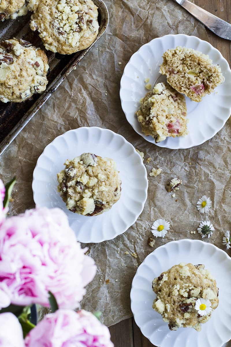 Three muffins on vintage, white plates, pink peonies in the bottom left corner. Flatlay.