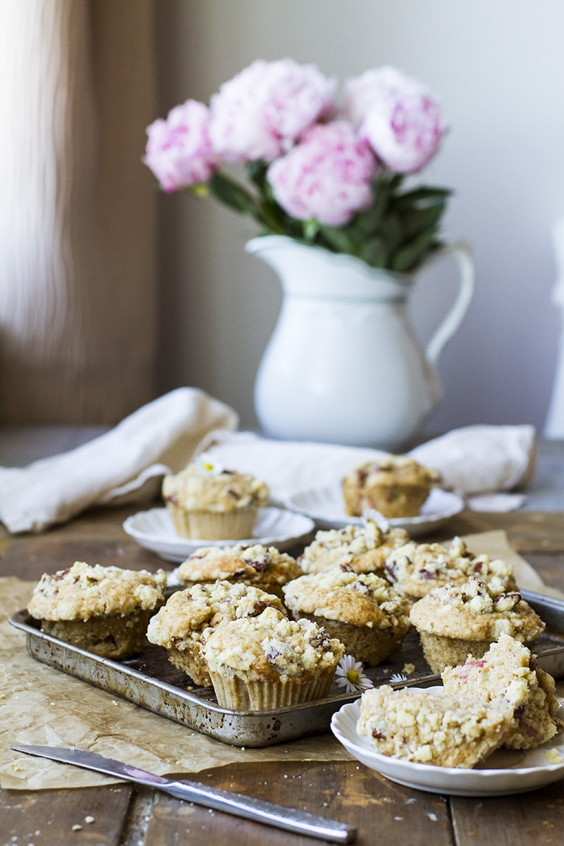 A baking sheet with baked rhubarb muffins, pink peonies in the background.