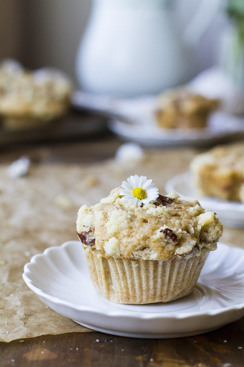 One muffin with crumb topping on a vintage, white plate.