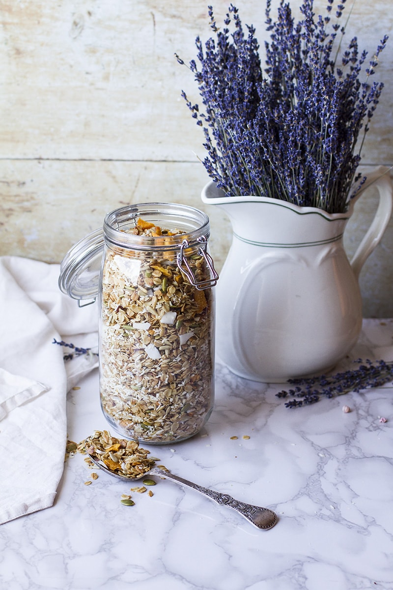 A big glass jar with granola and a vase with lavender flowers in the background.
