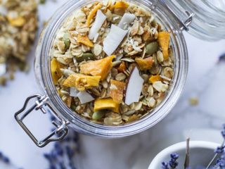A glass jar with coconut mango granola seen from above.