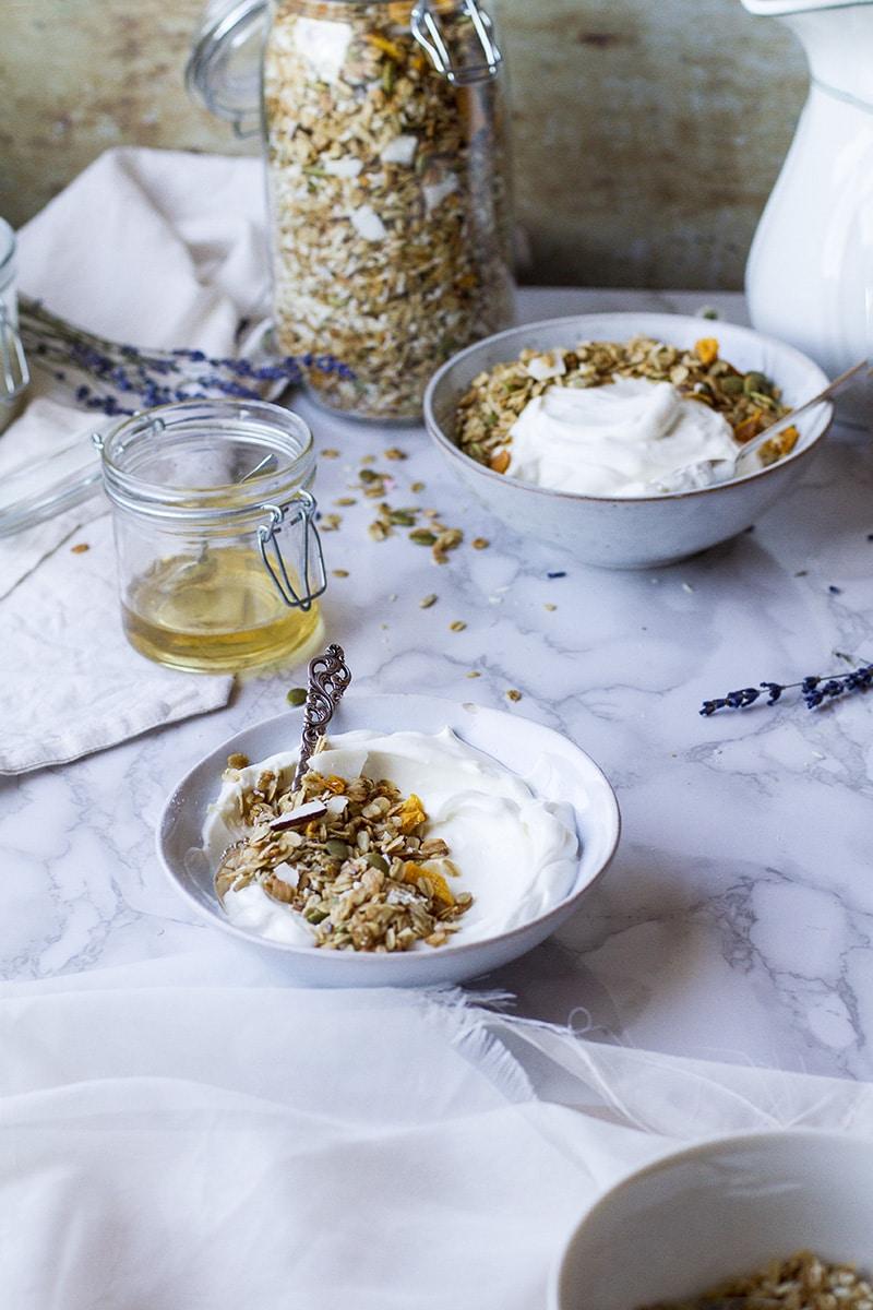 Two bowls with greek yogurt and granola.