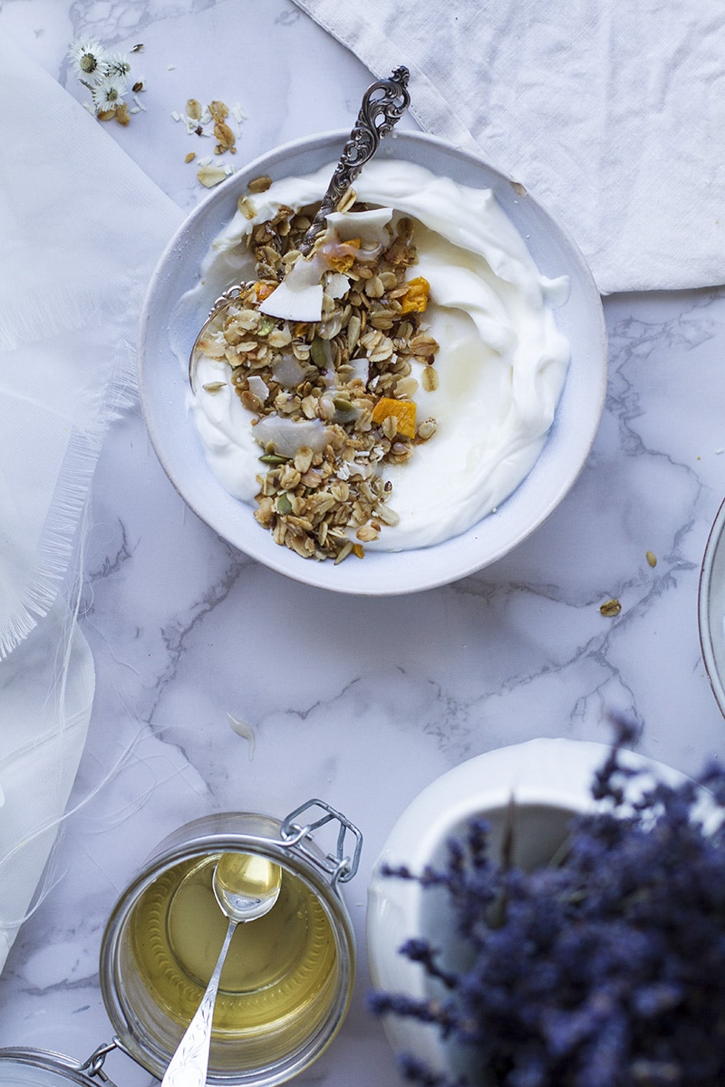 A blue bowl with Greek yogurt and granola, seen from above.