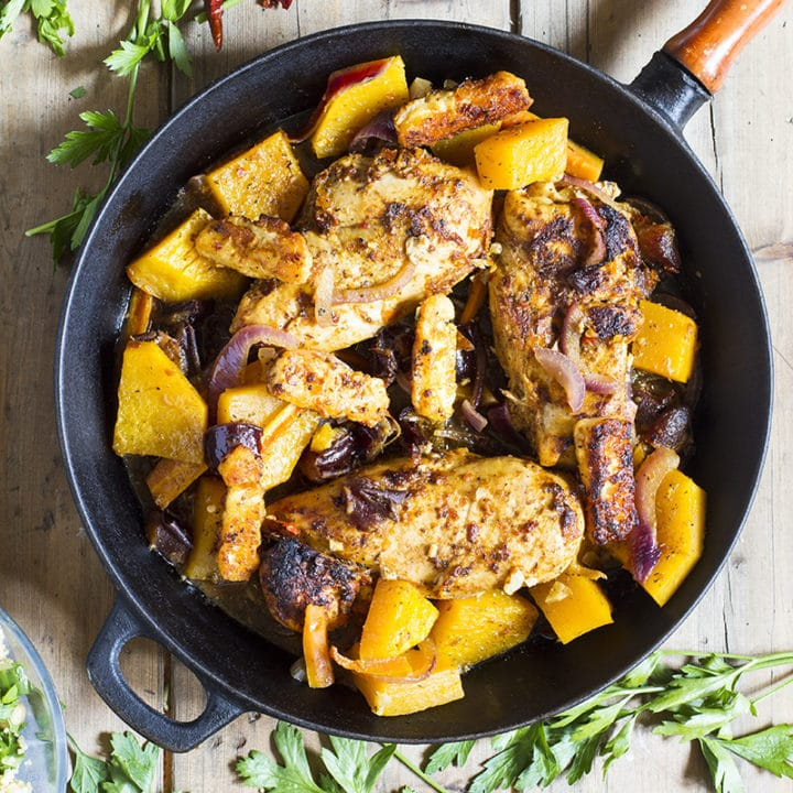 Chicken breast and butternut squash in a skillet.