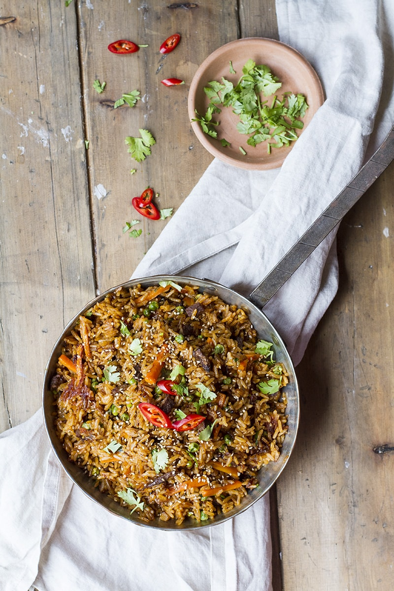 Small skillet with fried rice garnished with sliced red chilli.
