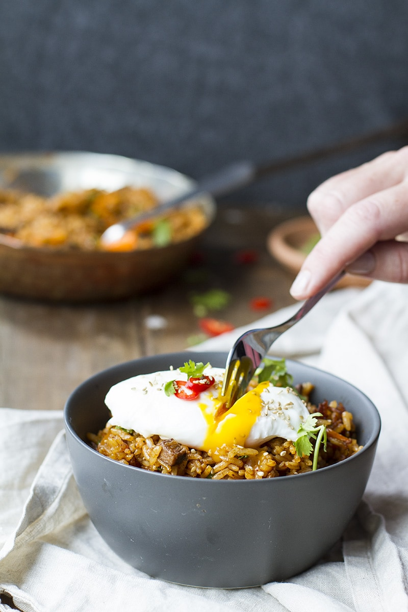 Hand taking a fork into the runny poached egg over fried rice.