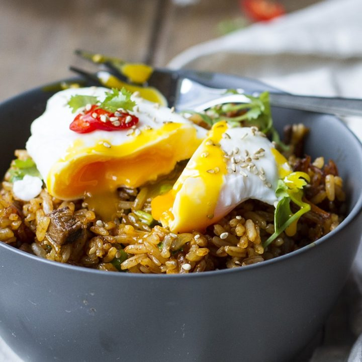 A dark grey bowl with fried rice and a runny poached egg on top.