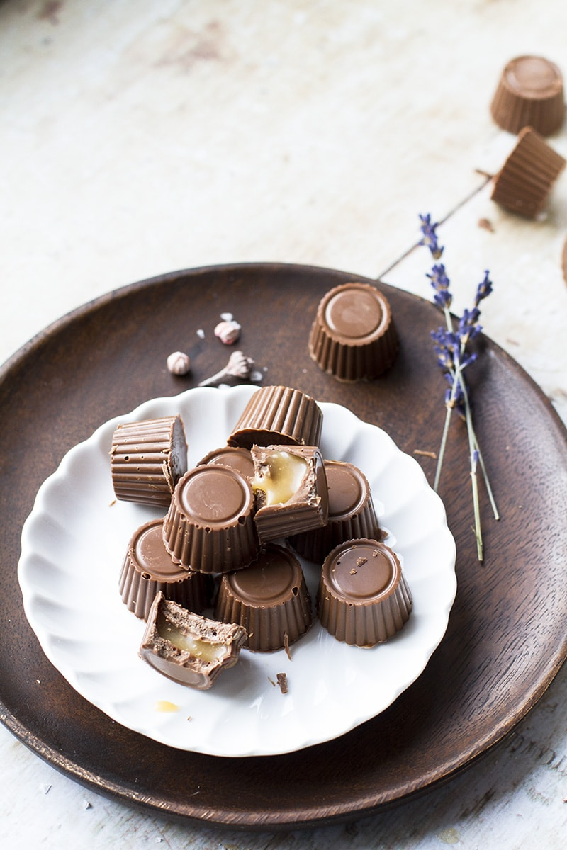 Vintage white plate with milk chocolates and caramels, dried lavender as decor.
