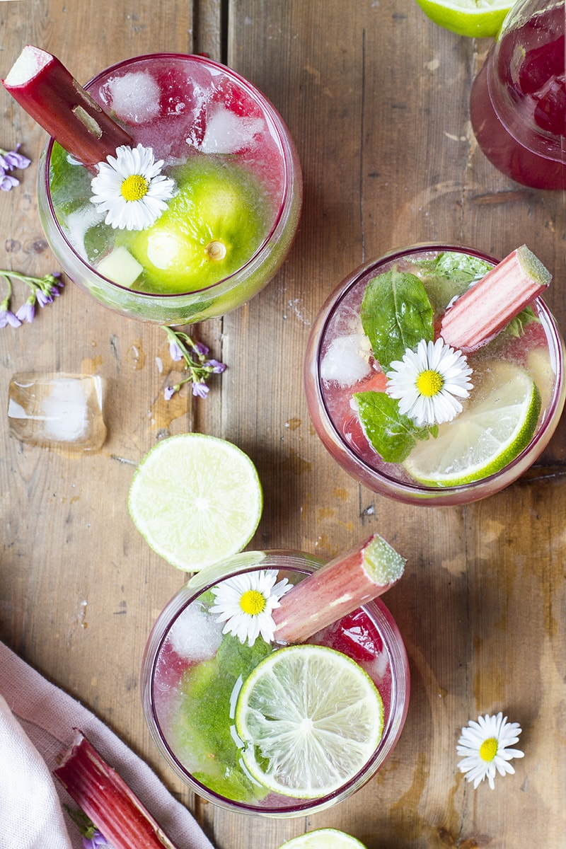 Three red cocktails seen from above, garnished with lime slices, rhubarb stalks and small flowers.