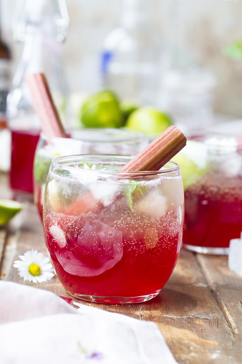 Close-up of a round glass with rhubarb Moscow mule and rhubarb stalks.
