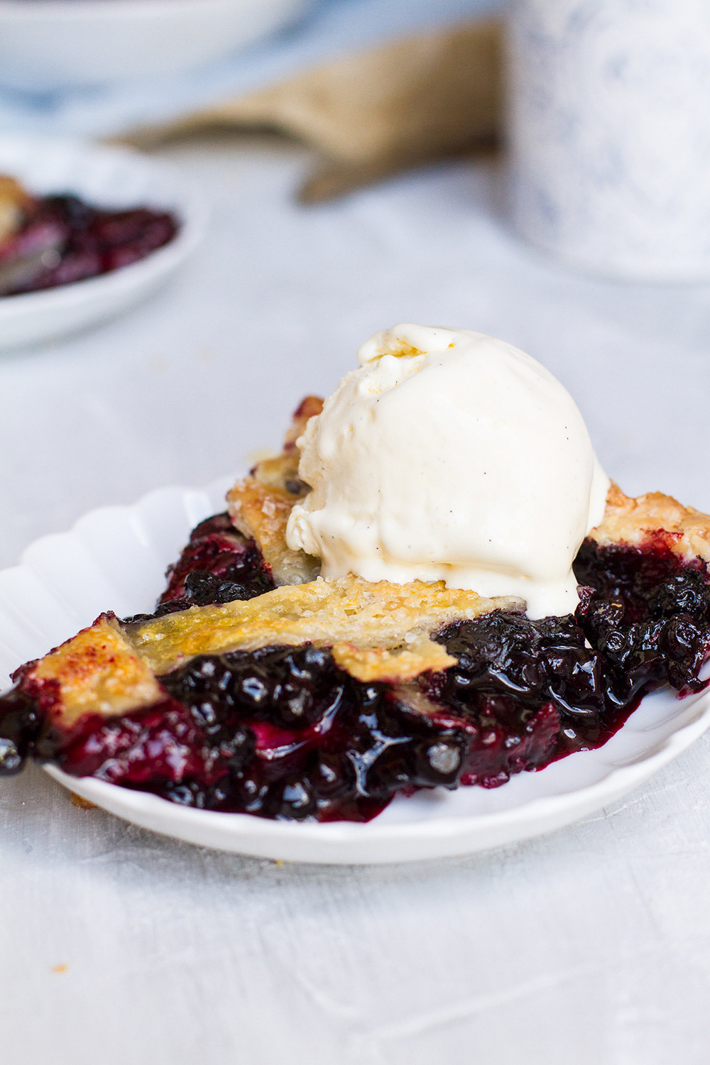 Slice of blueberry pie with slightly runny, uncooked blueberry filling.
