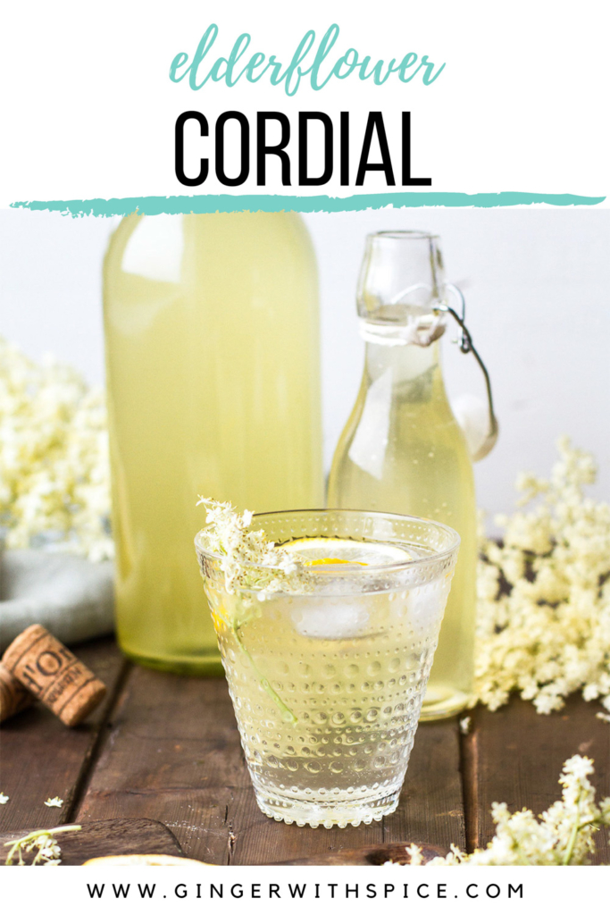 Homemade elderflower cordial in a clear glass with lemon wedge. Pinterest pin.