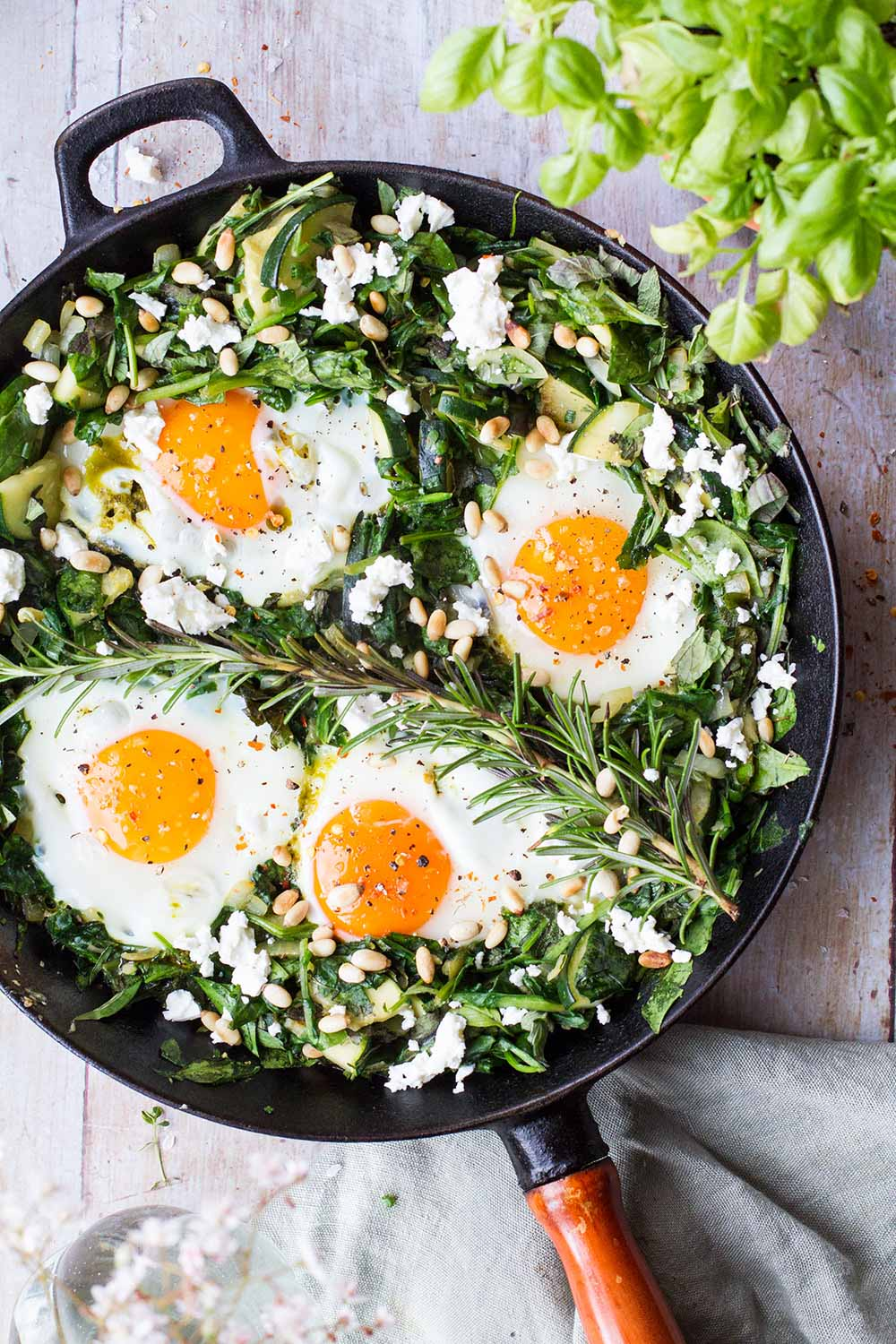 Cast iron skillet with green spinach bed and four sunny-side-up eggs.