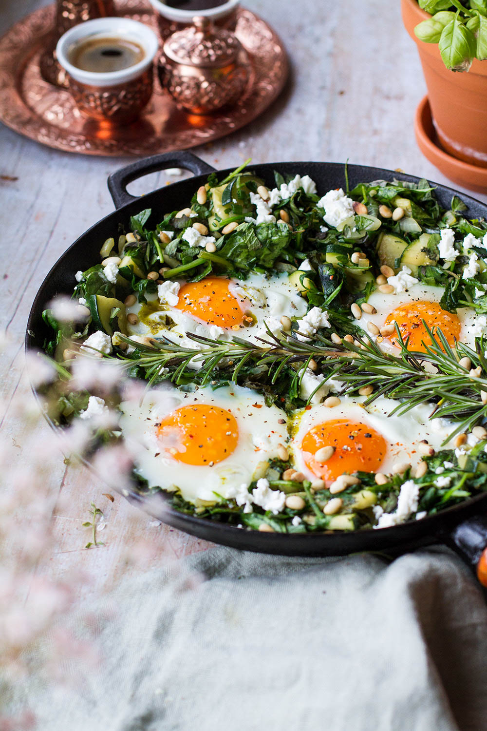 Four sunny-side-up eggs in a bed of greens in a skillet.