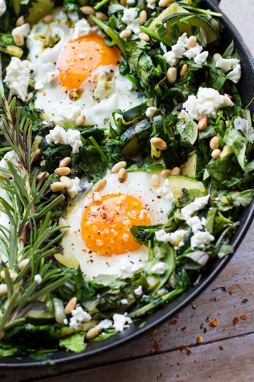 Close-up of the skillet showing two eggs, fresh rosemary and a bed of spinach.