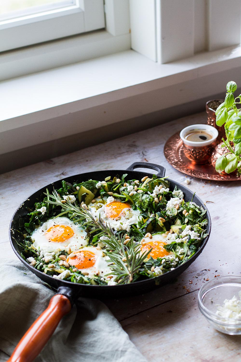 Skillet seen from a distance, with four eggs on top spinach and herbs.
