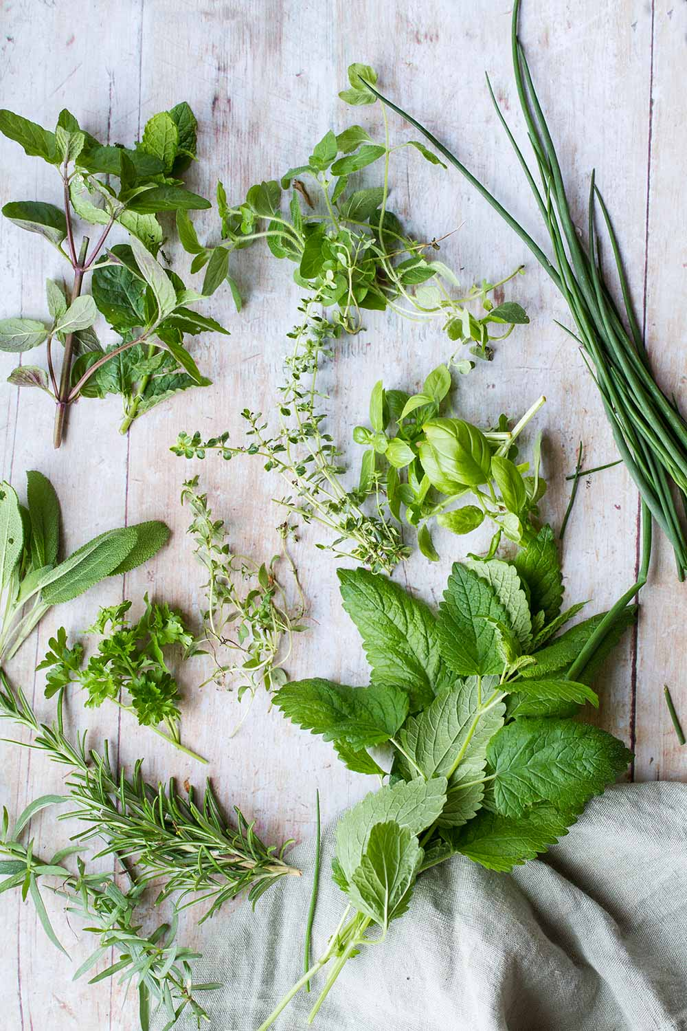 11 different herbs on a wooden table.