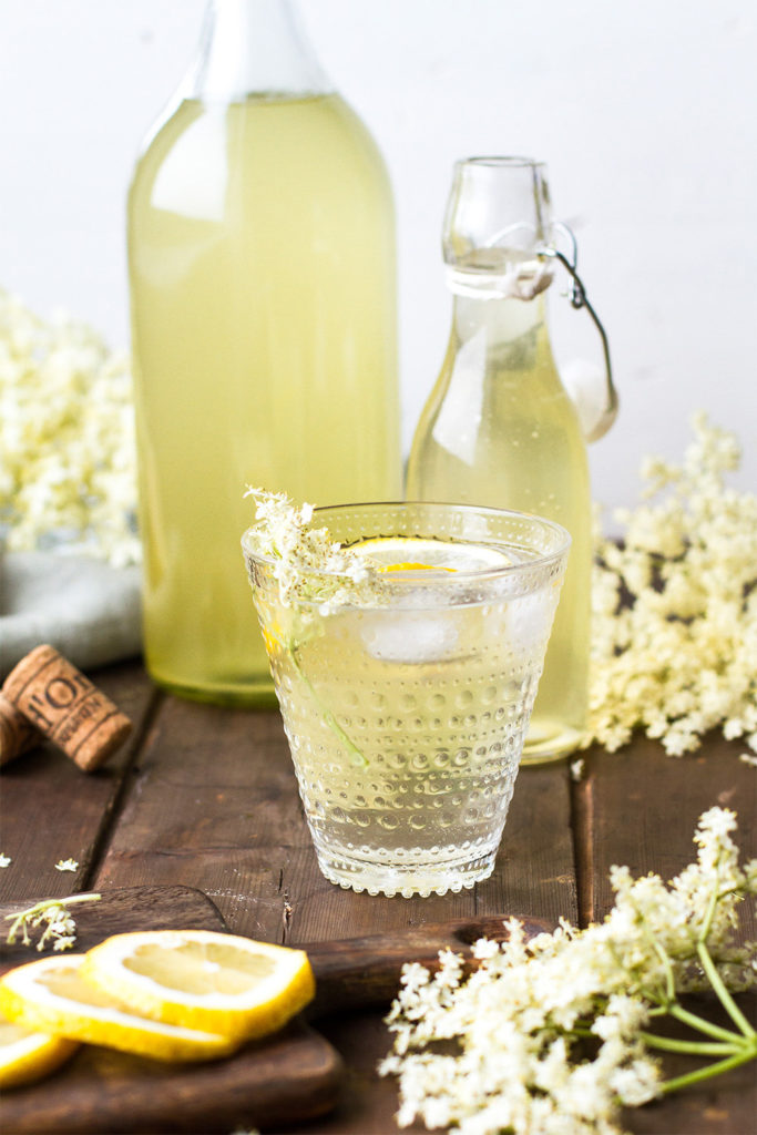 Homemade elderflower cordial in a clear glass with lemon wedge.