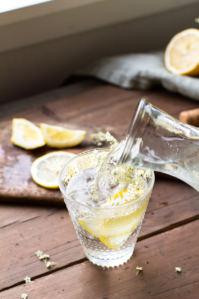 Pouring cordial into a glass with lemon wedge.