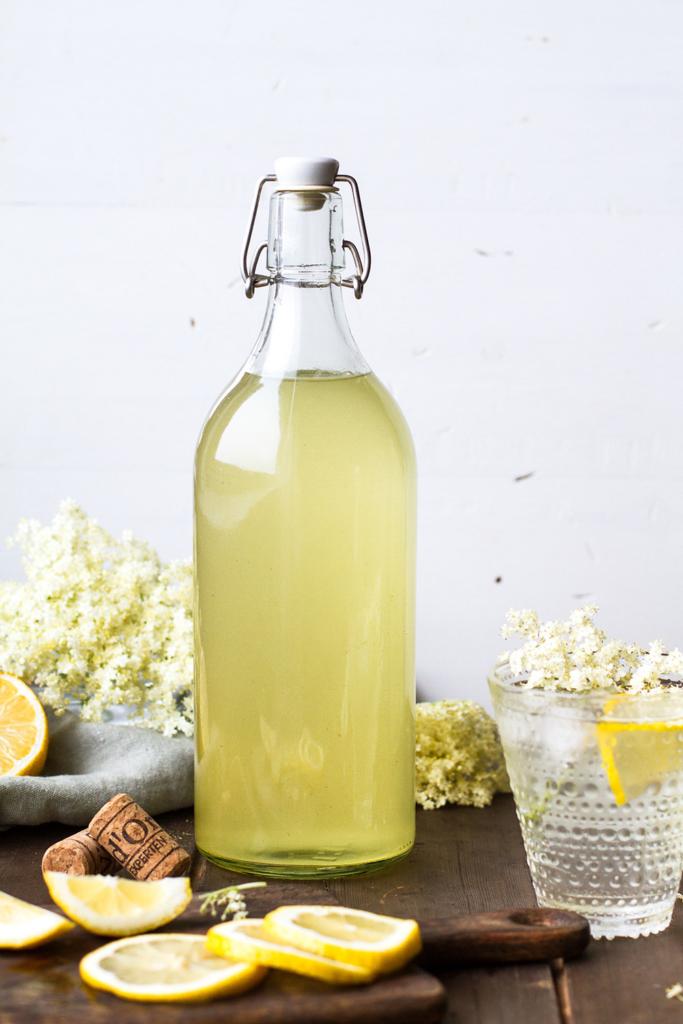 A large glass bottle with elderflower cordial.