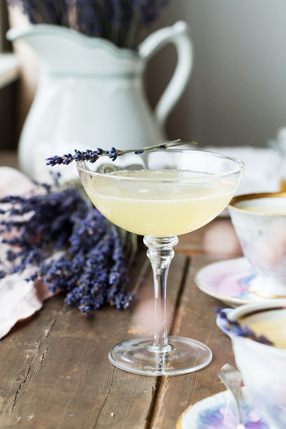 Coupé glass with yellow cocktail, garnished with dried lavender.