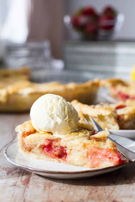 Slice of peach pie with ice cream on top.