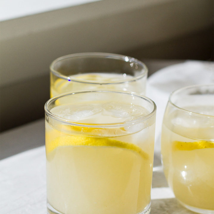 Three glasses with guava white tea and lemon wedges.
