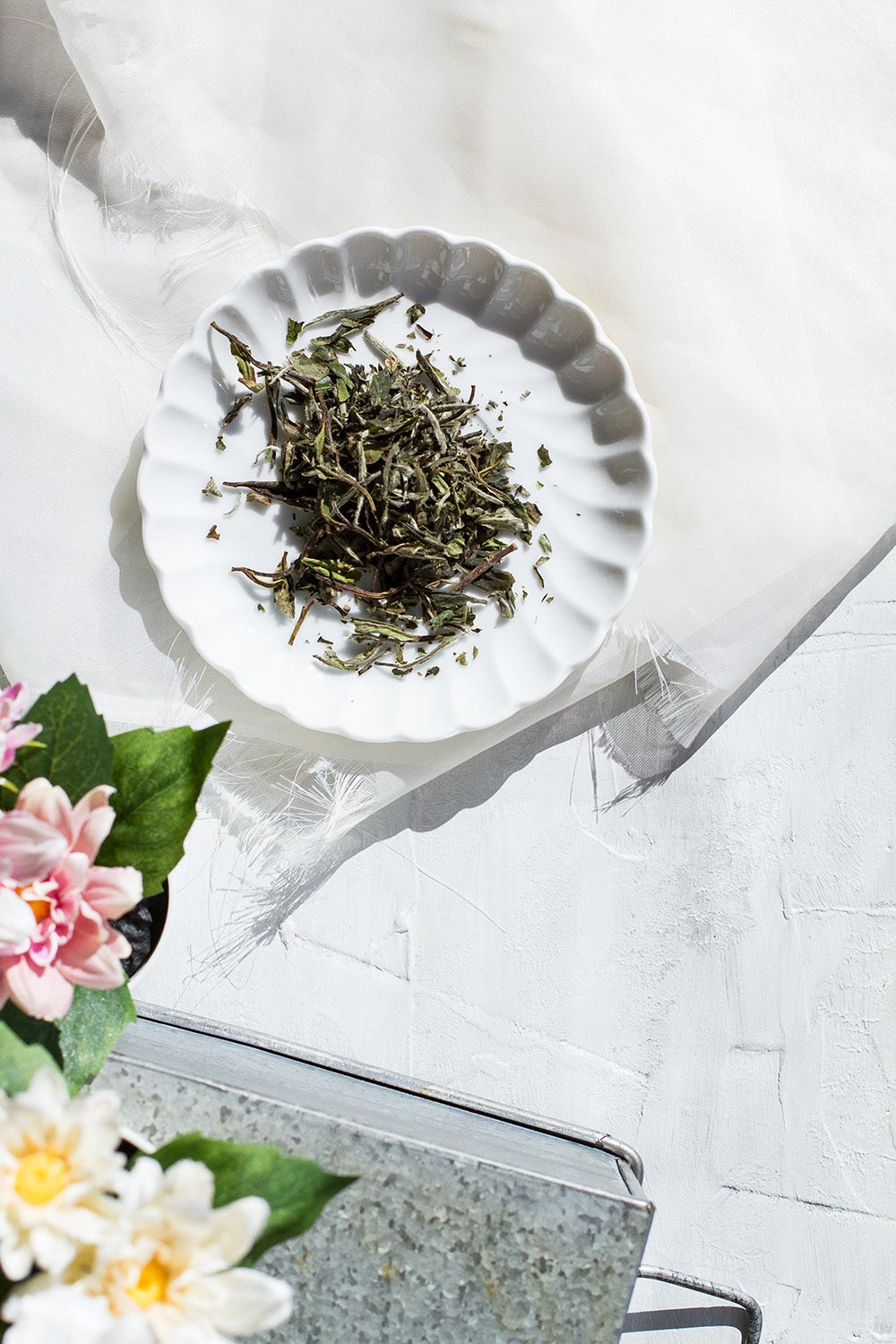 A vintage plate with white tea leaves.