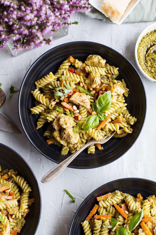 Dark bowls with chicken pesto pasta seen from above.
