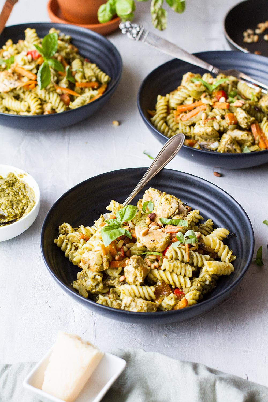 Three dark bowls with the chicken pasta dish.