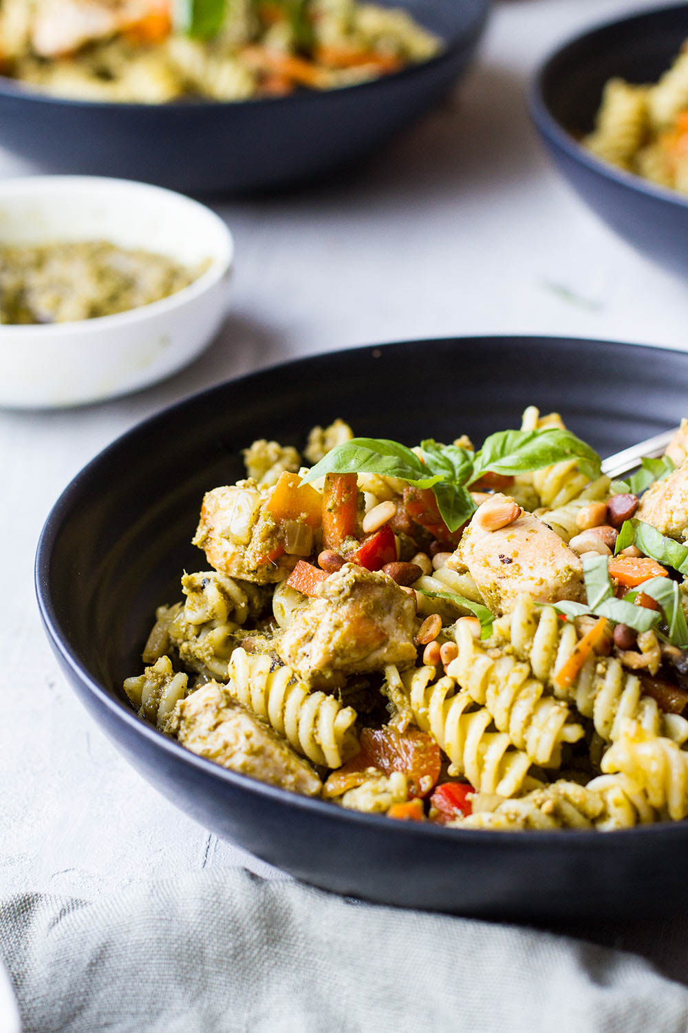 A dark bowl with pasta, vegetables and pesto.