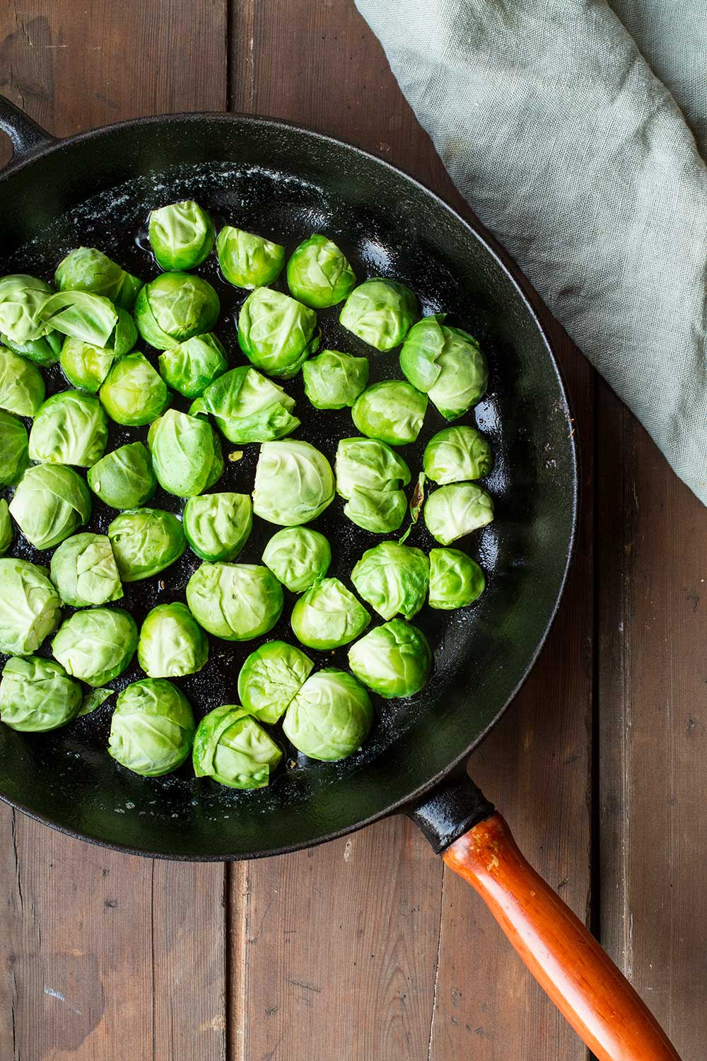 Brussels sprouts with cut side down in a cast iron skillet.