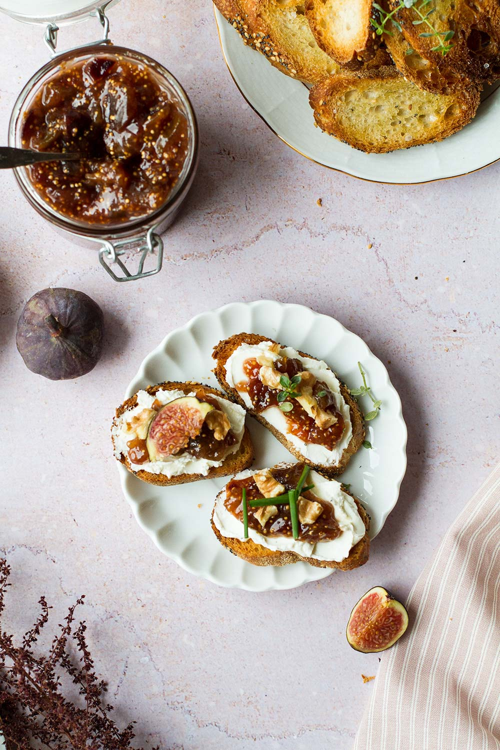Three crostini with goat cheese and fig jam on a vintage plate.
