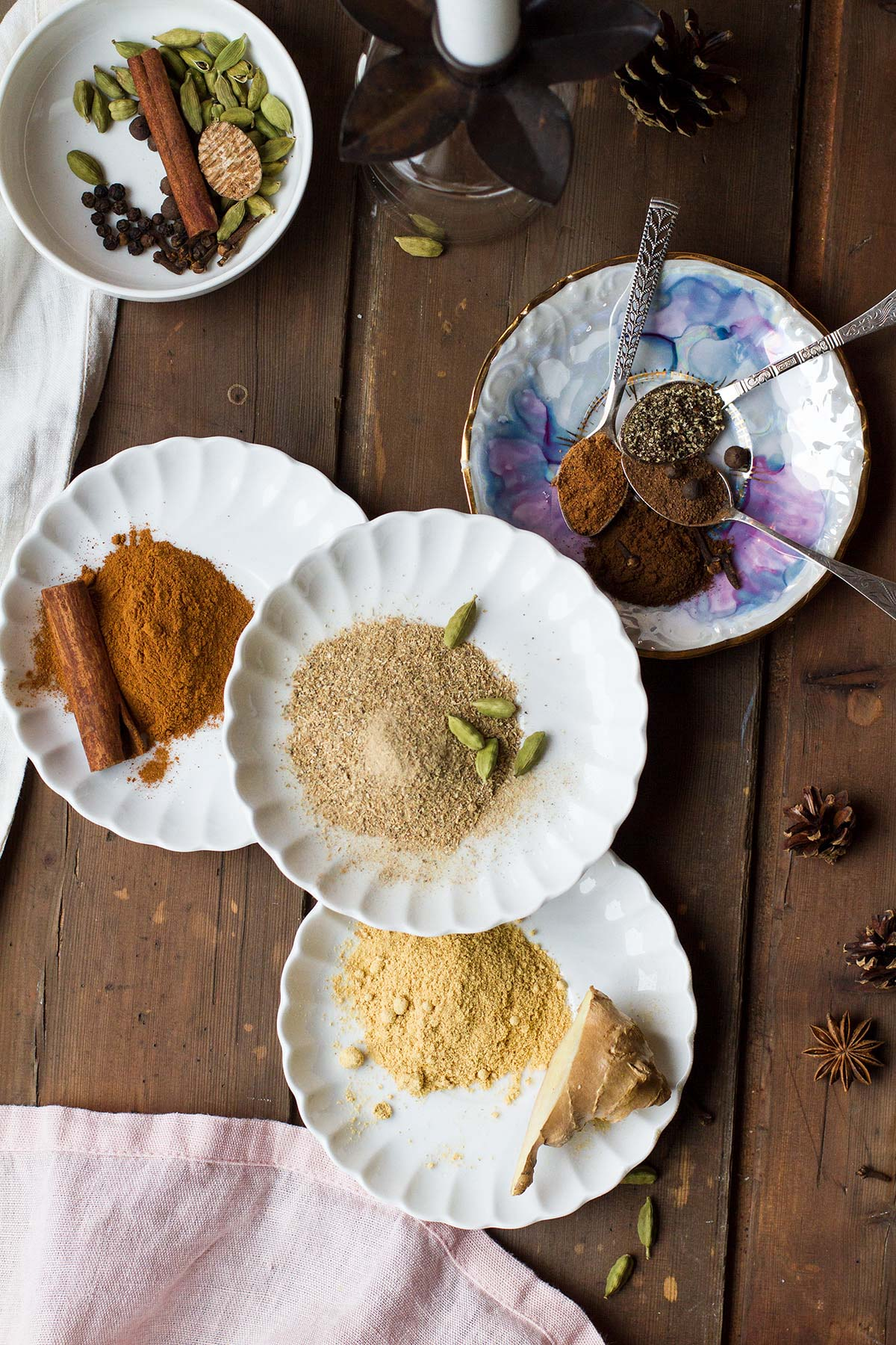 4 plates with different spices to make chai.