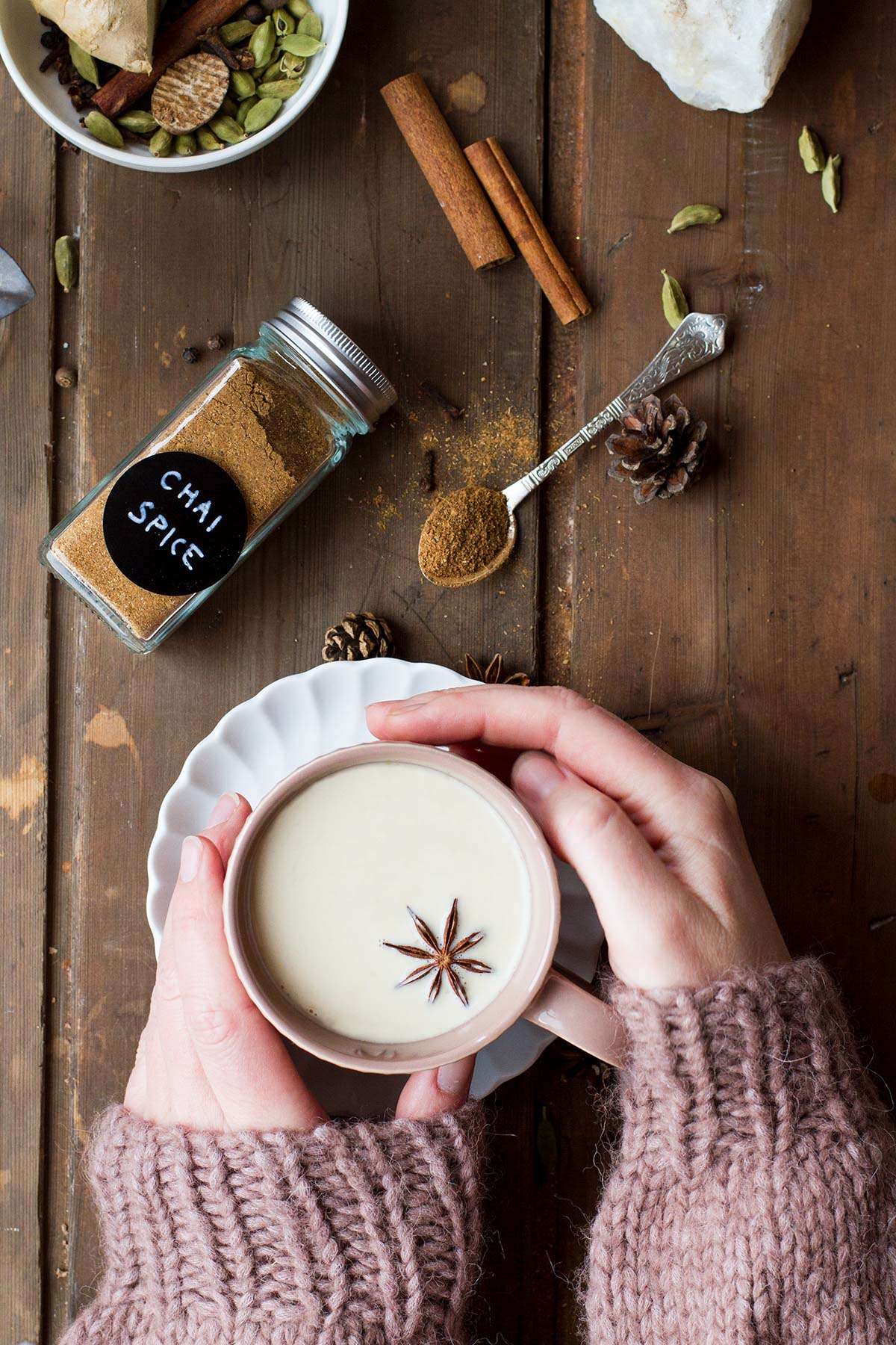 Hands holding a pink mug with chai tea latte.