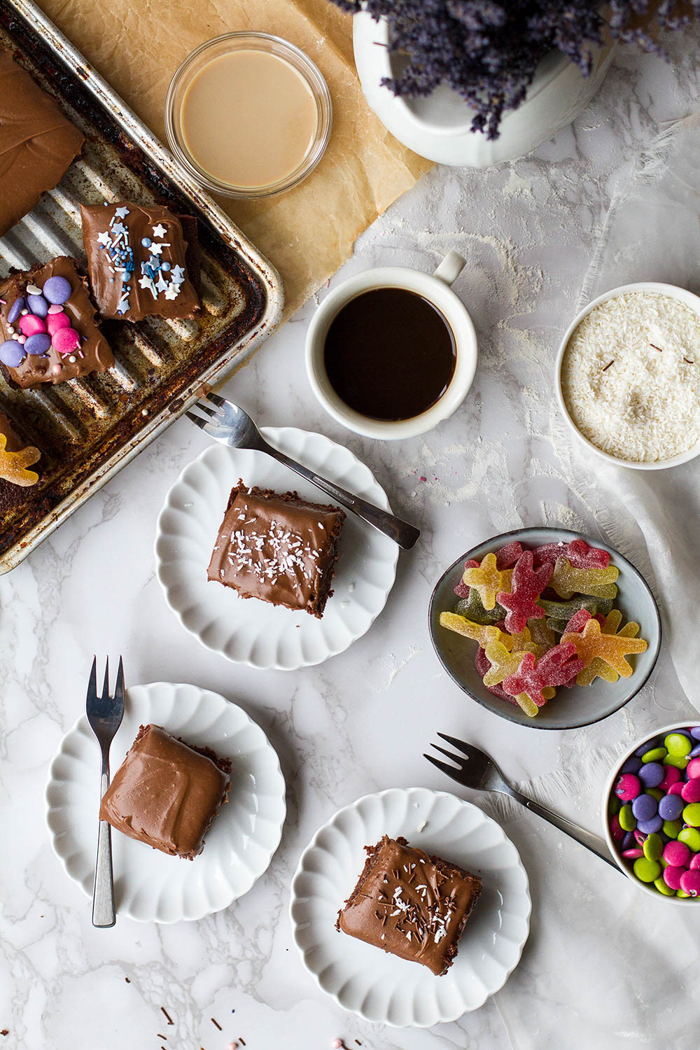 Marble table with several vintage plates with square slices of chocolate cake.