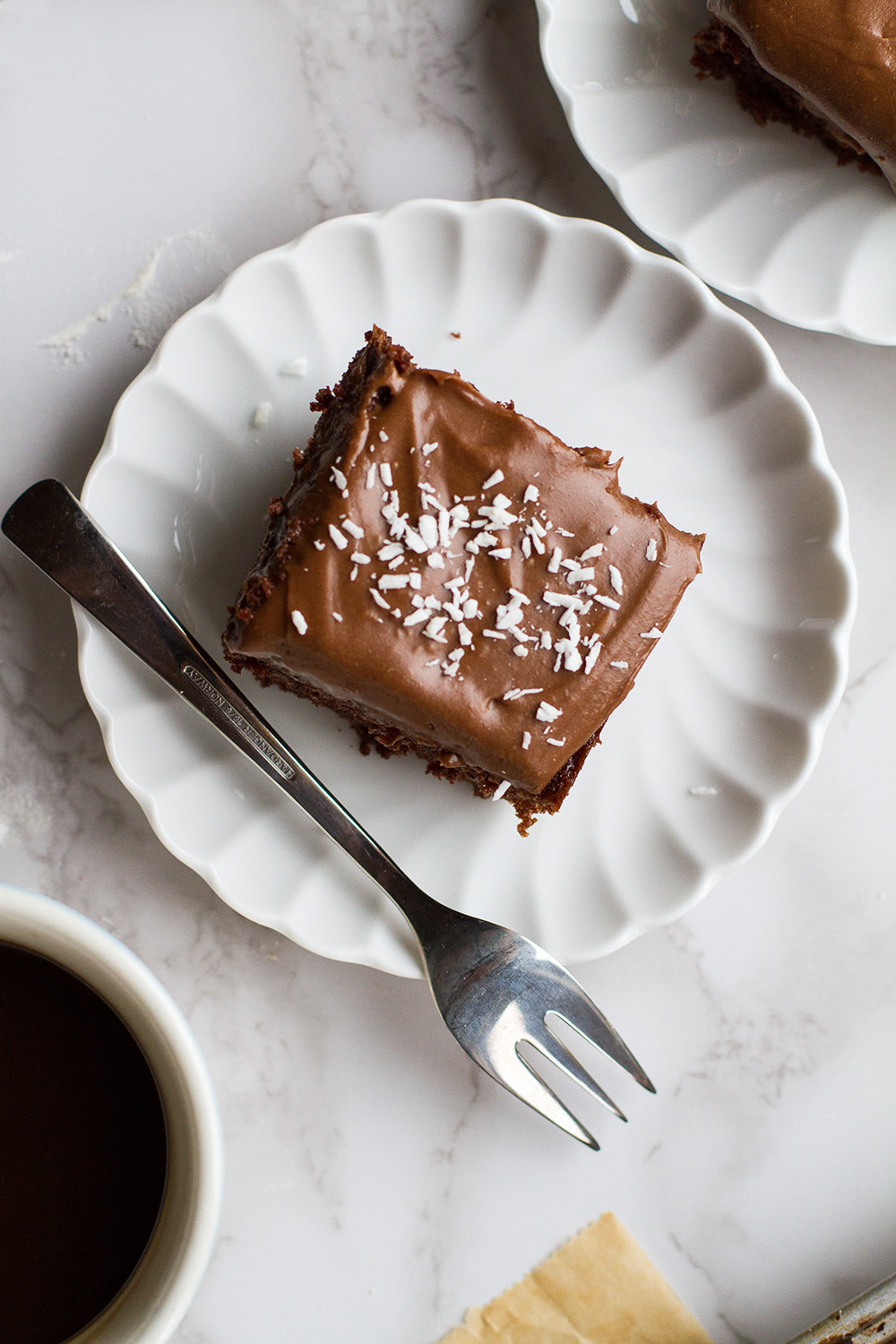 Slice of chocolate cake with shredded coconut as topping.
